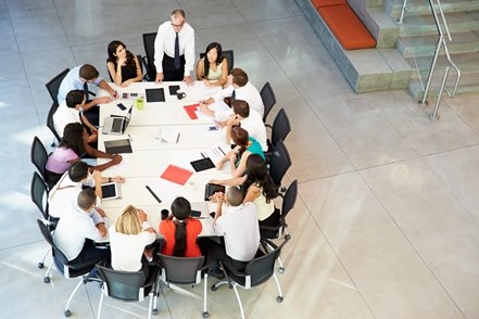 Team of professional men and women working together in an office setting at a round table