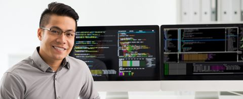 male data analytics professional smiling at camera with computer in background displaying data